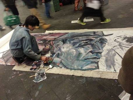 This artist was painting a portrait of the performance artists above.